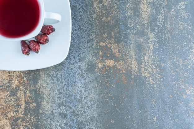 Tasse de thé aux églantiers sur fond de marbre.