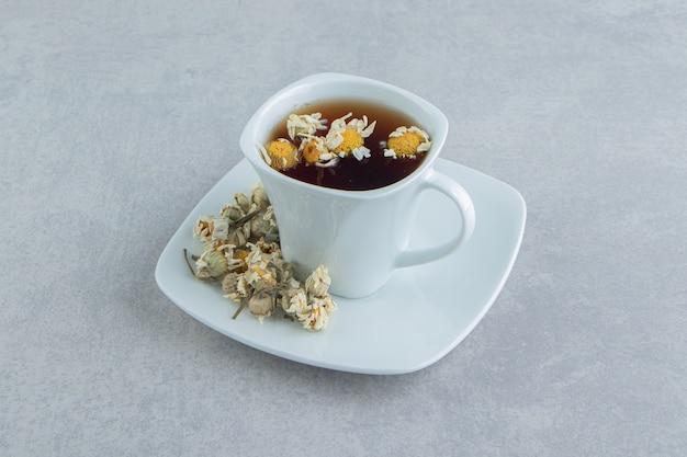 Tasse de thé aux fleurs de camomille séchées.