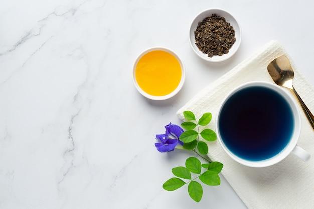 Tasse de thé aux fleurs de pois papillon avec du miel sur la table