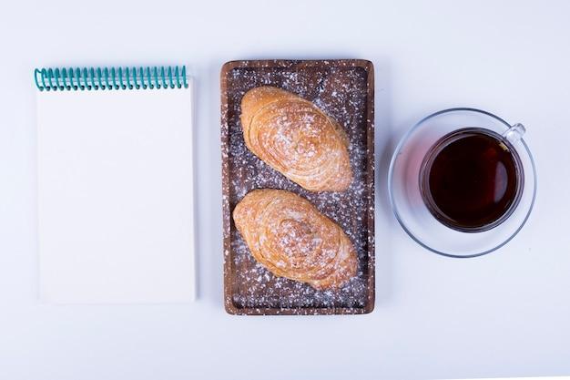 Une tasse de thé avec badamburas, un cahier vierge de côté dans la plaque sur fond de bois blanc