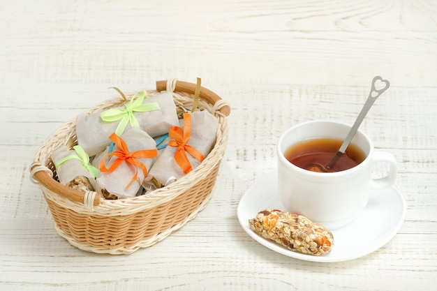 Tasse de thé et barre de muesli. panier en osier avec barres