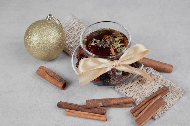 Tasse de thé, bâtons de cannelle et boule de fête sur table blanche. photo de haute qualité