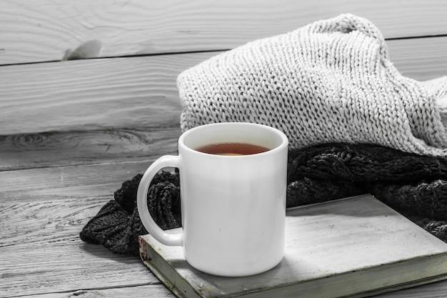 La tasse de thé sur un beau fond en bois avec pull d'hiver, vieux livre, hiver, automne, gros plan