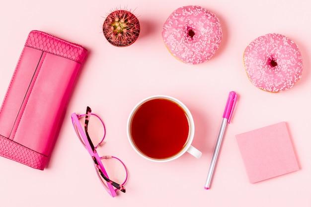 Tasse de thé avec des beignets sur fond rose pastel