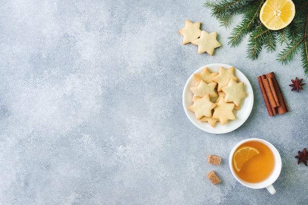 Tasse de thé et biscuits, branches de pin, bâtons de cannelle, étoiles d'anis