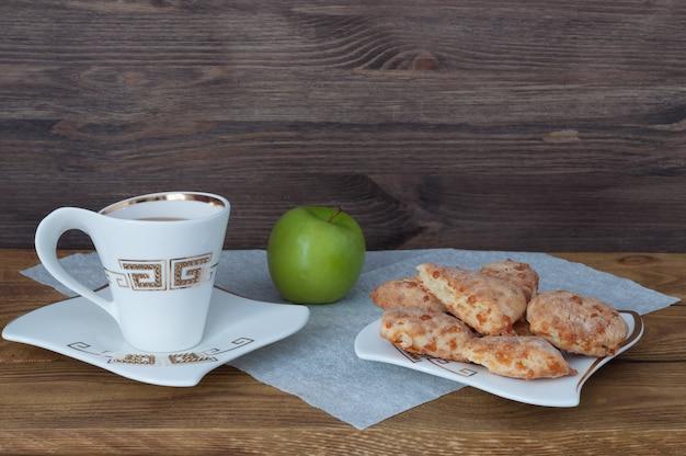 Une tasse de thé, des biscuits faits maison et une pomme sur un fond de planches de bois.