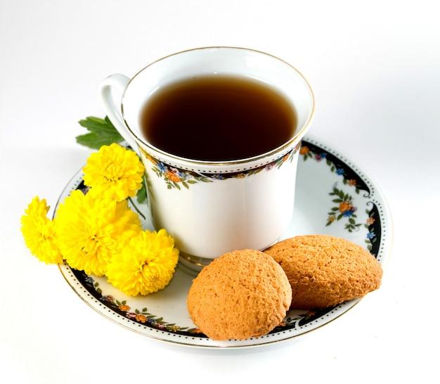 Tasse de thé avec des biscuits et des fleurs