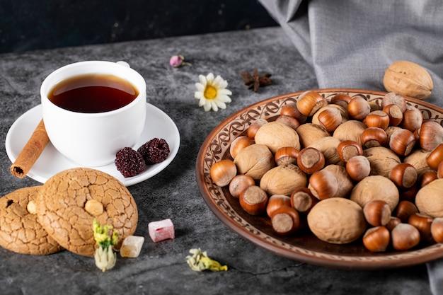 Une tasse de thé avec des biscuits et des noix