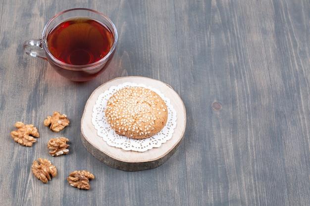 Tasse de thé, biscuits et noyaux de noix sur une surface en bois