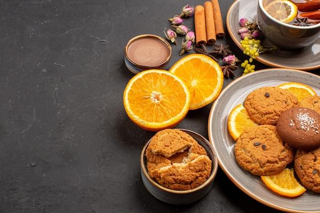 Tasse de thé avec des biscuits et des oranges fraîches en tranches sur noir