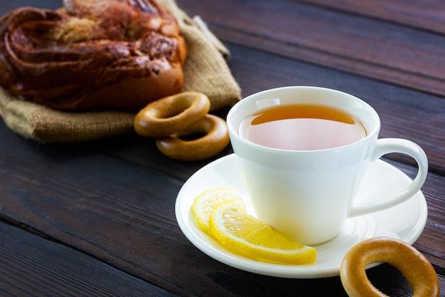 Tasse de thé blanche avec bagel au citron et biscuits pause déjeuner dans un café