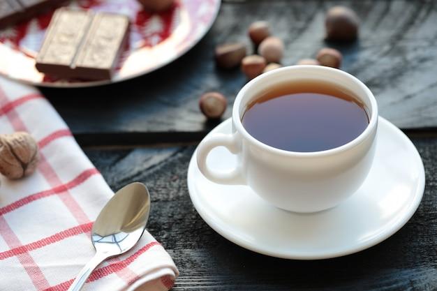 Une tasse de thé blanche avec une barre de chocolat et des noix autour.