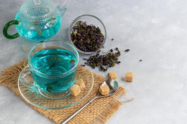 Une tasse de thé bleu chaud avec des fleurs de pois. pois bleus. pour une boisson saine, détoxifiant le corps. table grise.