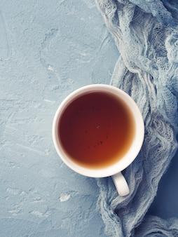 Tasse de thé sur bleu avec des fleurs et textile