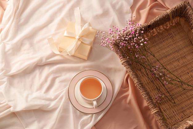 Tasse de thé, boîte-cadeau et fleurs sur plateau sur fond de tissu clair