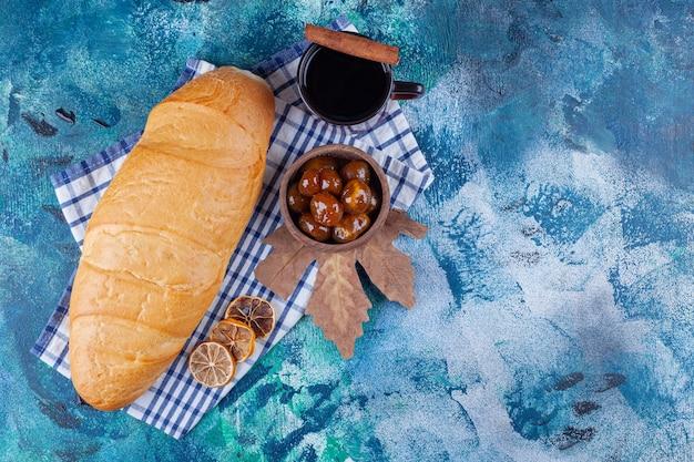 Une tasse de thé, un bol de confiture et du pain de mie sur un torchon, sur le bleu.