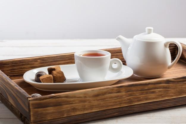 Tasse de thé avec des bonbons au chocolat sur table en bois