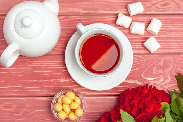 Tasse de thé avec des bonbons et des fleurs sur une table en bois