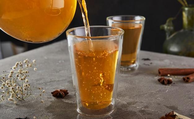 Tasse de thé bouillonnant coulant d'une théière sur un gris