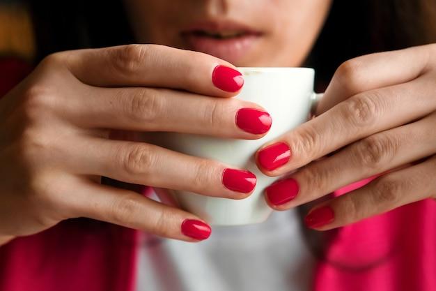 Une tasse de thé ou de café dans les mains d'une femme, manucure rose, gros plan