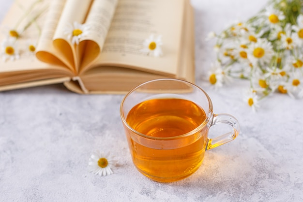 Une tasse de thé à la camomille et un bouquet de marguerites