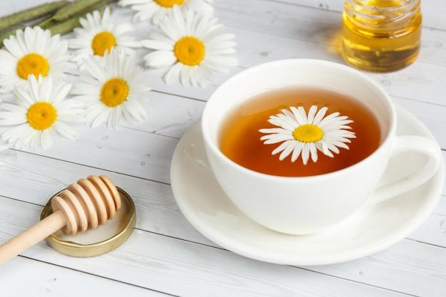 Tasse de thé à la camomille sur fond en bois blanc