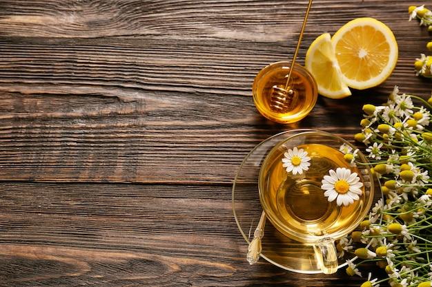 Tasse de thé à la camomille sur fond de bois