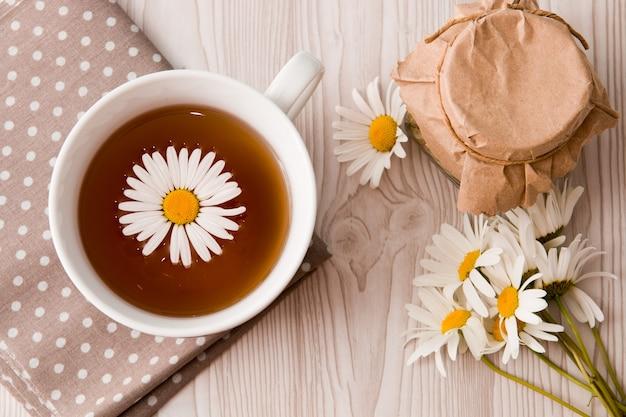 Tasse de thé et de camomille et pot sur un tissu à pois thé peut dentelle fleurs beige gris marron orange