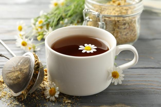 Tasse de thé à la camomille sur table en bois
