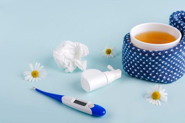 Tasse de thé à la camomille, thermomètre, lingettes en papier froissé et spray pour le nez et la gorge qui coule sur fond bleu. maladies saisonnières et traitement du rhume, de la grippe, de la chaleur. prévention des virus.