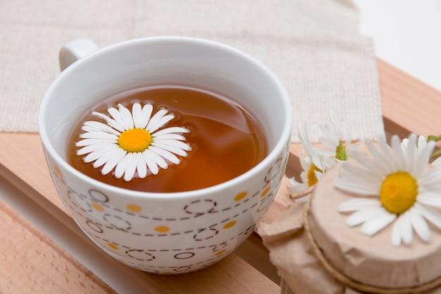 Tasse de thé à la camomille sur un tissu beige avec des marguerites sur un plateau en bois surface blanche isolation vue de dessus copie espace