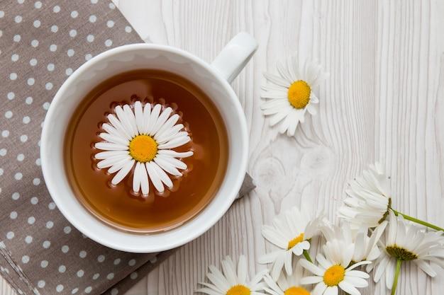 Tasse de thé à la camomille sur un tissu à pois marron sur une surface blanche vue de dessus copie espace