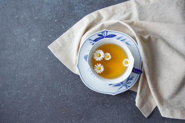Une tasse de thé à la camomille avec vue de dessus en tissu