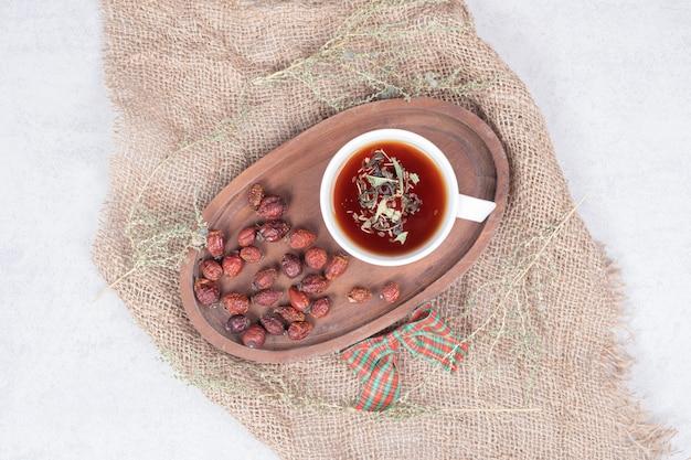Tasse de thé et canneberges séchées sur toile de jute. photo de haute qualité