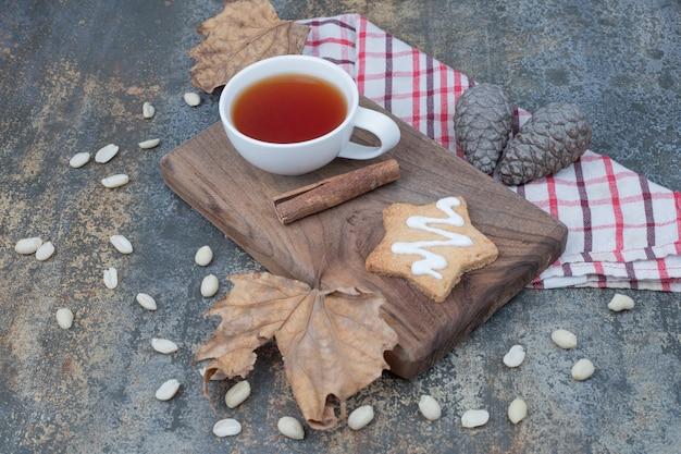 Tasse de thé, cannelle et biscuits en pain d'épice sur une plaque en bois. photo de haute qualité