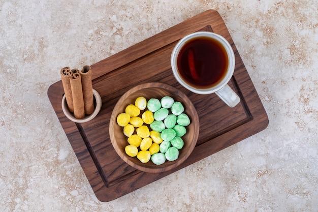 Tasse de thé, cannelle et bonbons sur planche de bois