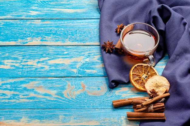 Tasse de thé à la cannelle chaude aromatique sur une table en bois