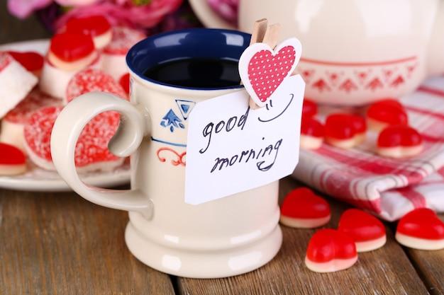 Tasse de thé avec carte qui dit bonjour sur gros plan de table