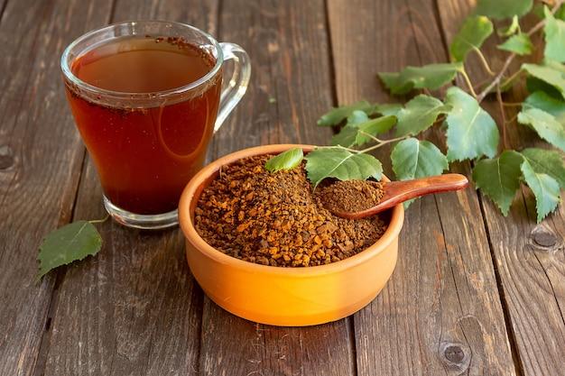 Une tasse de thé chaga sur une table sombre, des tranches de chaga et une brindille de bouleau, mise au point sélective