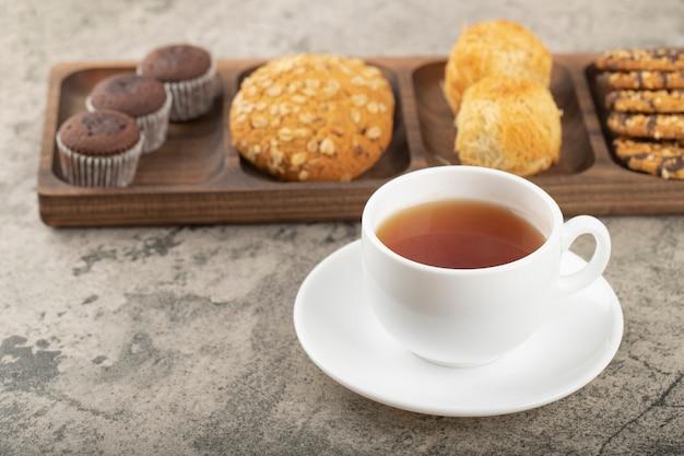 Tasse de thé chaud avec assiette de divers bonbons sur la table.