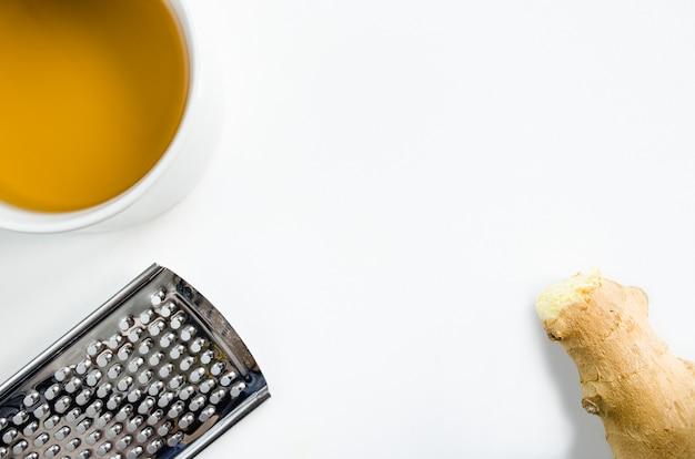 Tasse de thé chaud au gingembre et grattoir avec copie espace dans une image conceptuelle de la prévention du rhume et de la grippe