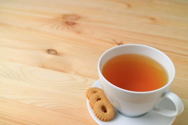 Tasse de thé chaud et biscuits servis sur une table en bois naturel
