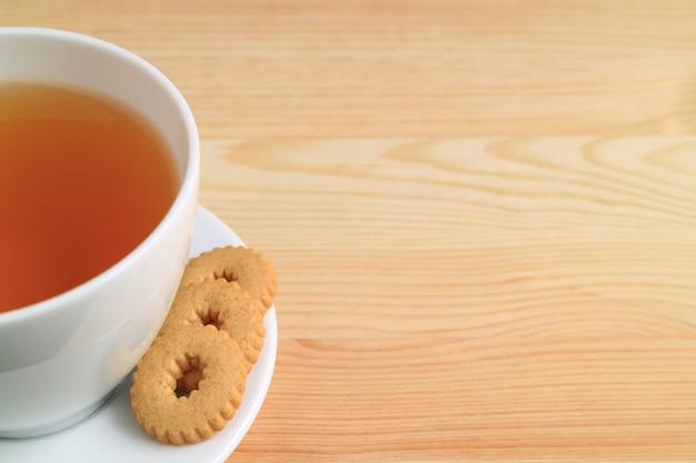 Une tasse de thé chaud et des biscuits sur une table en bois naturel
