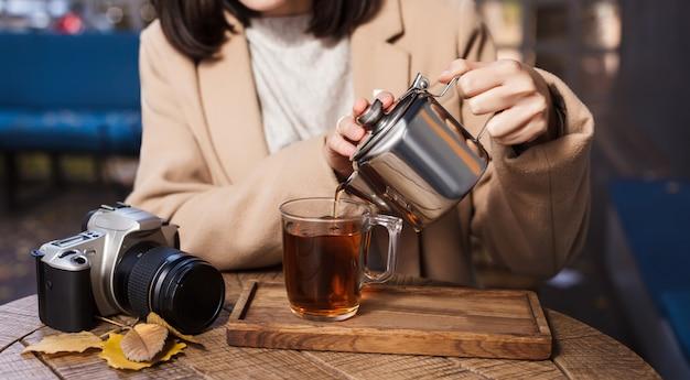 Une tasse de thé chaud, une caméra et des feuilles jaunes agrandi. fond d'automne mains de fille