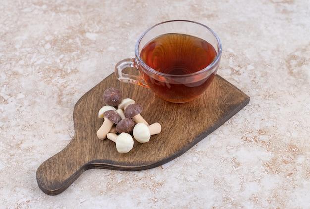 Une tasse de thé chaud avec des champignons sucrés sur une planche de bois