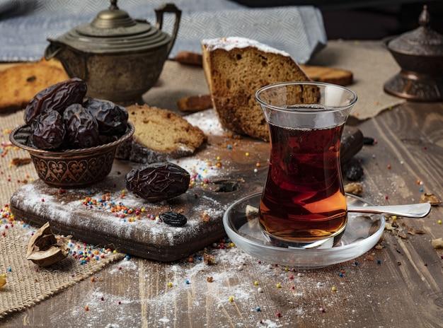 Une tasse de thé chaud avec des dates sur fond de bois.