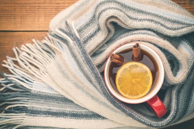 Une tasse de thé chaud est enveloppée dans une écharpe en laine. il y a un citron et deux bâtons de cannelle dans la tasse. vue de dessus.