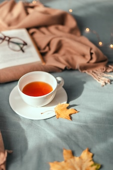 Tasse de thé chaud avec des feuilles d'automne et un décor de guirlande lumineuse, livre et verres sur plaid gris au lit
