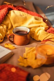 Tasse de thé chaud avec des feuilles d'automne et un décor de guirlande lumineuse sur un plaid marron au lit.