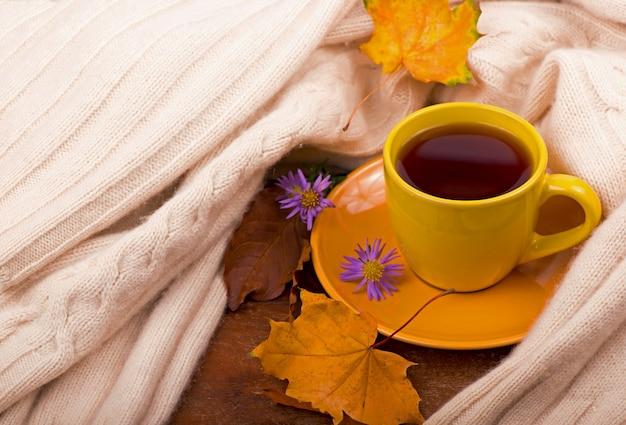 Tasse de thé chaud et feuilles d'automne, sur fond marron